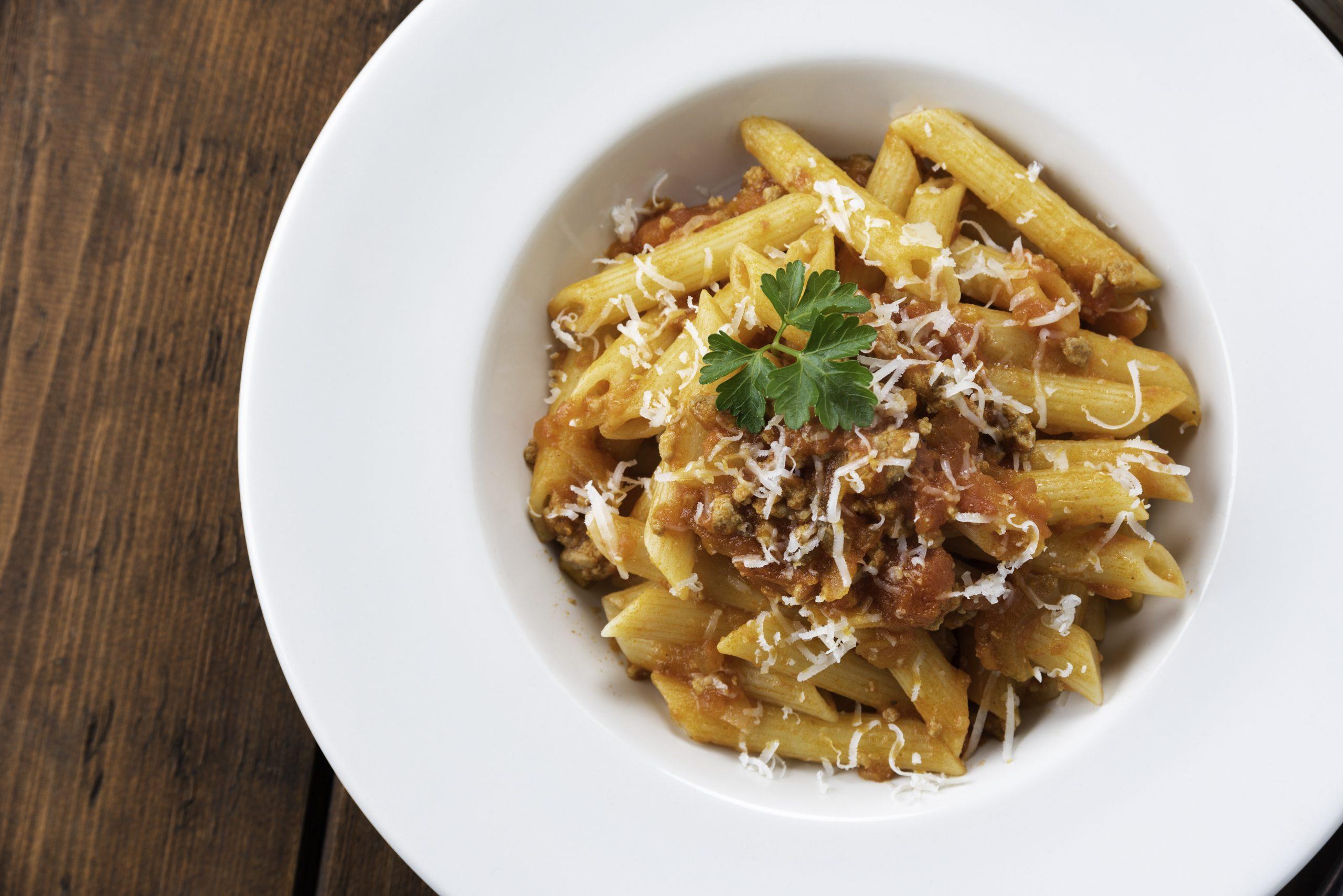 Piatto di deliziose penne con ragu alla bolognese, Cucina Italiana